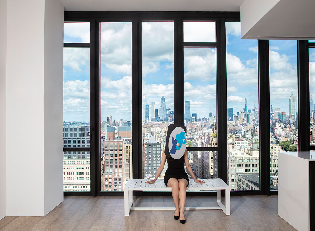 masked character sitting on top a white bench in the 111 Varick penthouse unit