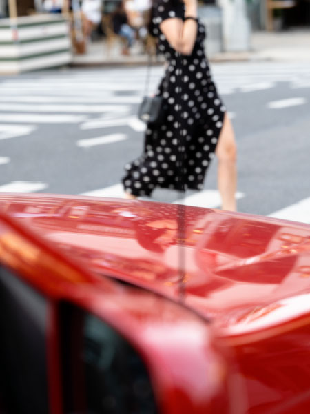 woman wearing polka-dot dress crossing street in front of red car